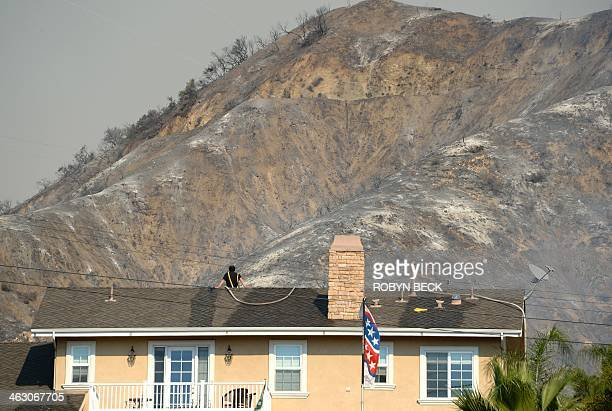 A homeowner keeps watch from his roof during the Colby Fire January 16 2014 in Azusa California The fastmoving Colby Fire originated early on...