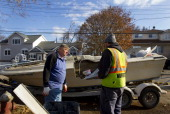 A homeowner left speaks with a FEMA representative while doing repairs on his boat in the Staten Island borough of New York US on Wednesday Nov 28...
