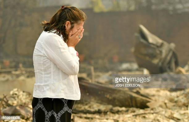 TOPSHOT Homeowner Martha Marquez looks over her burned home in Santa Rosa California on October 10 2017 Firefighters encouraged by weakening winds...
