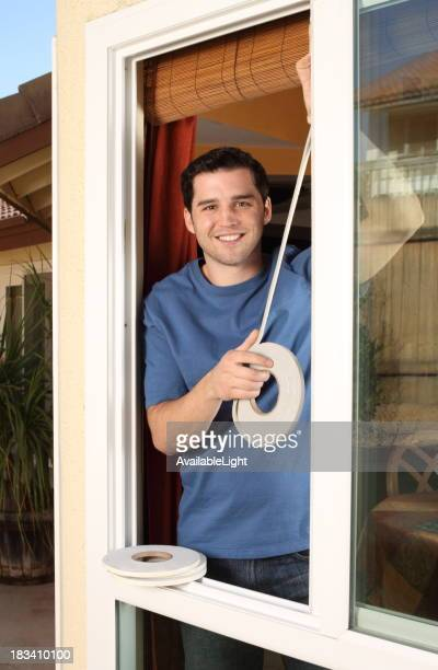 Homeowner Smiles While Installing Weather Stripping in Window