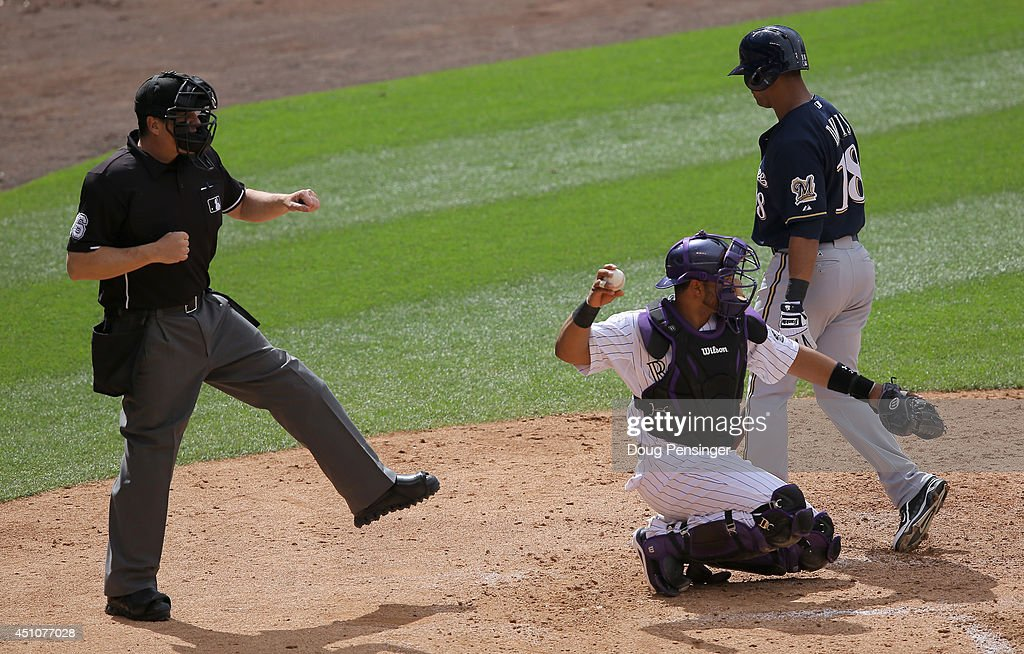Homeplate umpire Mike DiMuro calls Khris Davis of the Milwaukee Brewers out on strikes as catcher Wilin Rosario of the Colorado Rockies returns the...