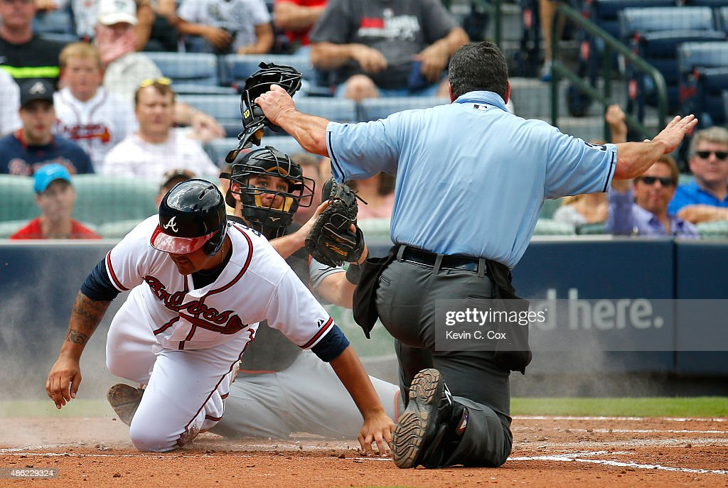 Homeplate umpire Rob Drake signals safe as Williams Perez of the Atlanta Braves scores past the tag of Jeff Mathis of the Miami Marlins on a...