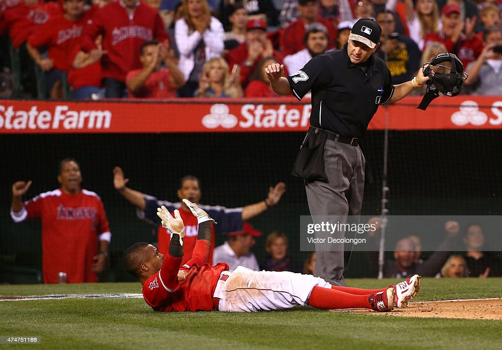 Homeplate umpire Scott Barry #87 signals <a gi-track='captionPersonalityLinkClicked' href=/galleries/search?phrase=Erick+Aybar&family=editorial&specificpeople=551376 ng-click='$event.stopPropagation()'>Erick Aybar</a> #2 of the Los Angeles Angels of Anaheim safe at home plate after a wild pitch by pitcher Tyson Ross #38 of the San Diego Padres (not in photo) in the fifth inning of the MLB game at Angel Stadium of Anaheim on May 25, 2015 in Anaheim, California. Aybar scored from third base.