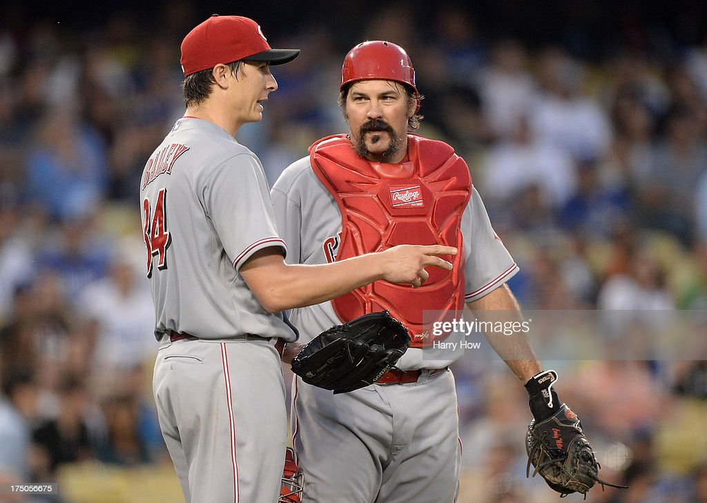 Homer Bailey #34 and Corky Miller #37 of the Cincinnati Reds meet on the mound during the third inning against the Los Angeles Dodgers at Dodger Stadium on July 26, 2013 in Los Angeles, California.