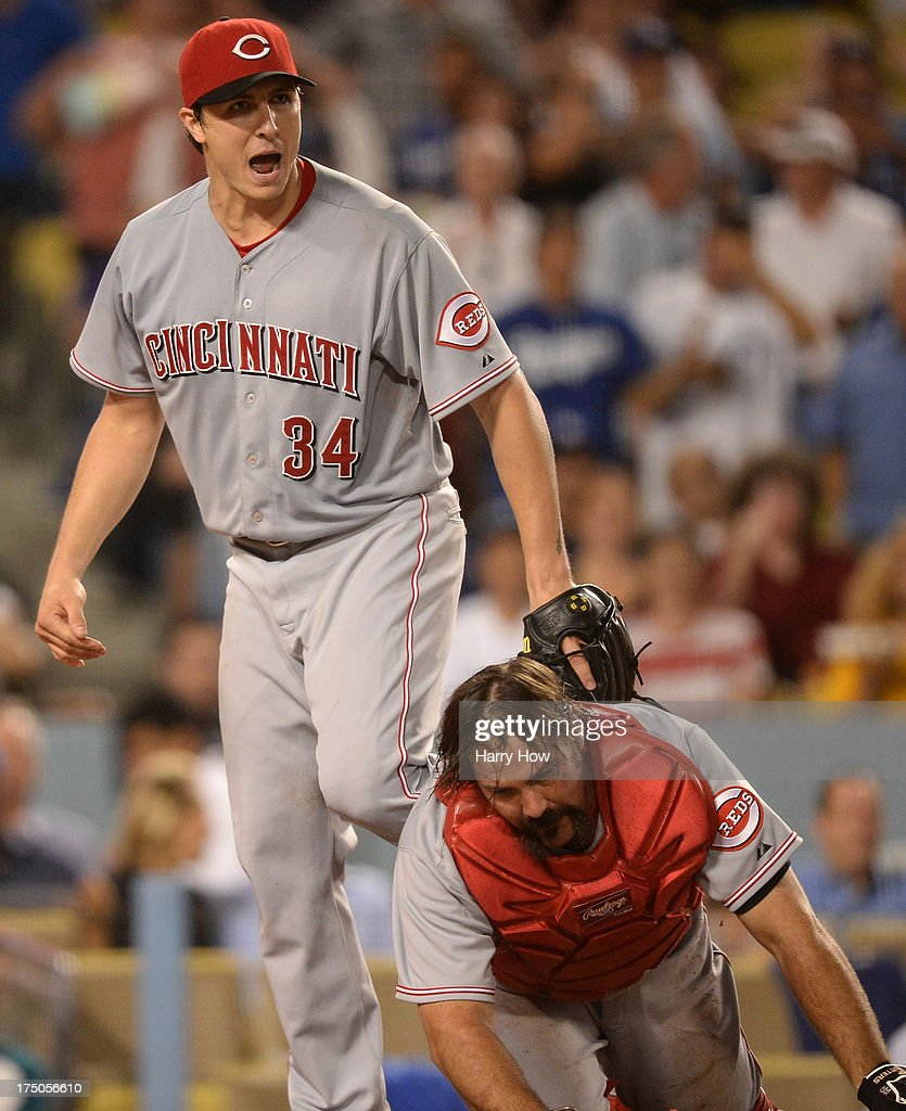 Homer Bailey #34 of the Cincinnati Reds and Corky Miller #37 react after Hanley Ramirez #13 of the Los Angeles Dodgers is called out at home during the fourth inning at Dodger Stadium on July 26, 2013 in Los Angeles, California.