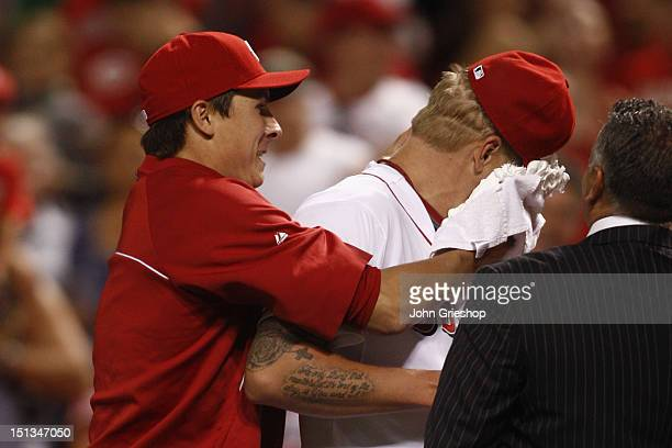 Homer Bailey of the Cincinnati Reds gives Mat Latos a shaving cream pie in the face after a victory against the Milwaukee Brewers at Great American...