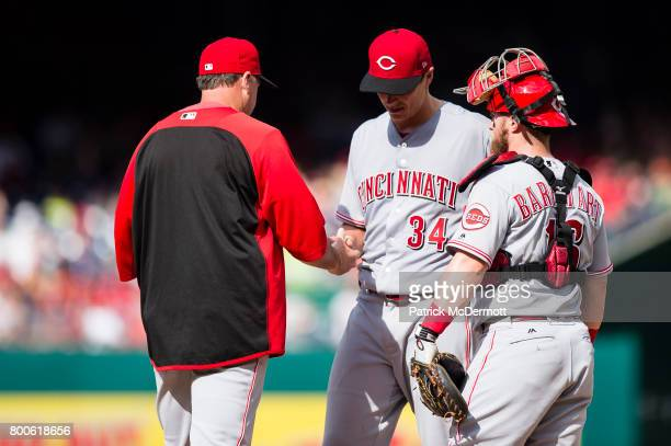 Homer Bailey of the Cincinnati Reds hands the ball to manager Bryan Price after being relieved in the second inning during a game against the...