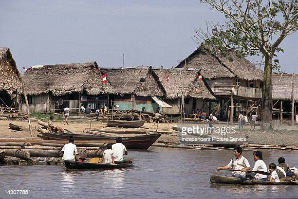 Homes and boats near Iquitos on the Amazon River in Peru the red and white flags on the building are the colors of the Inca Empire and represented in...