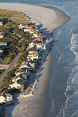 This is a picture of houses dangerously close to the ocean shot from the air.  You can see ocean in the late afternoon light on a warm sunny day coming very close to beach homes.  The waves seem calm