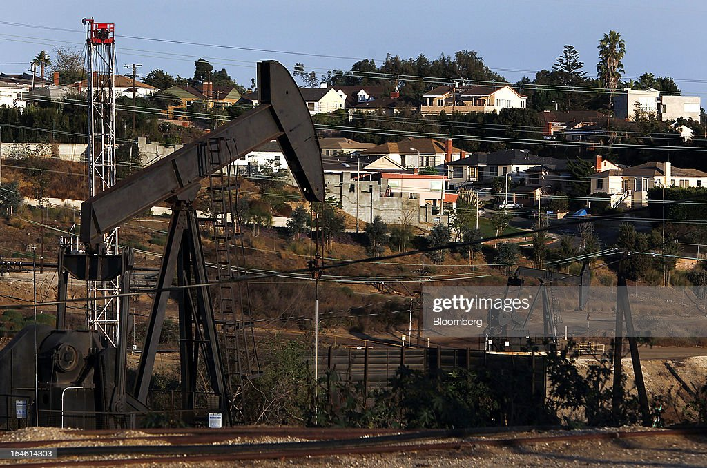Homes stand while pumpjacks operate near a hydraulic fracturing (fracking) test well at the Inglewood Oil field in Los Angeles, California, U.S., on Thursday, Oct. 19, 2012. The Inglewood Oil Field is a steady source of domestic oil and natural gas as well as the second most productive oil field in the entire L.A. Basin. Photographer: Patrick T. Fallon/Bloomberg via Getty Images