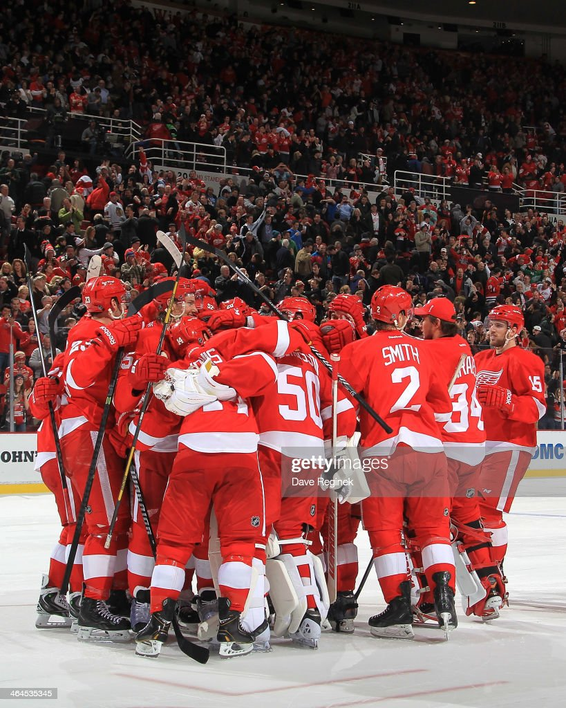Hometown fans celebrate and members of the Detroit Red Wings swarm teammate Jonas Gustavsson #50 after stopping the 6th and final shot in a shootout to win an NHL game against the Chicago Blackhawks on January 22, 2014 at Joe Louis Arena in Detroit, Michigan. Detroit defeated Chicago 5-4 in a shootout