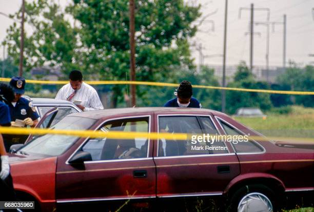 DC homicide detectives examine evidence in a car at a murder crime scene Washington DC 1996 The victim's body was found in the parked car