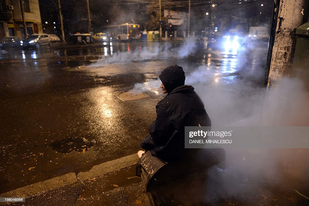 A homless person warms-up at an air pit of a heating system in Bucharest, on December 9, 2012. Romania's centre-left governing coalition has comfortably won a weekend parliamentary poll with nearly 60 percent of the vote, partial results showed on December 10, 2012.