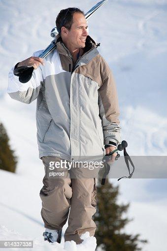 Homme Souriant homme souriant qui marche avec ses skis stock photo | thinkstock