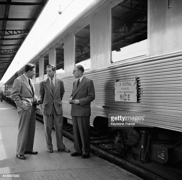 Hommes discutant devant le train Mistral sur la ligne ParisNice en France le 20 août 1954