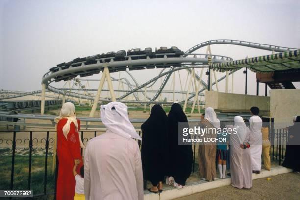 Hommes et femmes en costume traditionnel à côté de montagnes russes au Parc d'attraction de l'an 2000 à Koweit City en mai 1984 au Koweit
