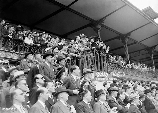 Hommes femmes civils et militaires venus assister à la course hippique à l'hippodrome de Longchamp à Paris France le 20 mai 1945