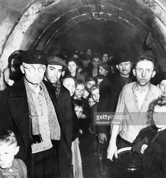 Hommes femmes et enfants allemands les yeux équarquillés et l'air haggard entassés à l'entrée du tunnel où ils se protègent des bombes en Allemagne...