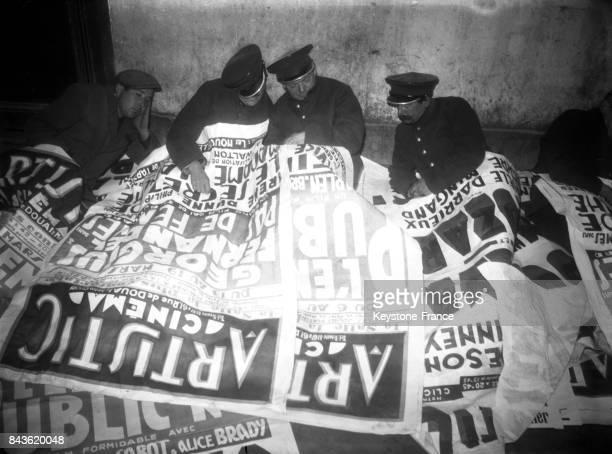 Hommessandwiches occupant les locaux de la société qui les emploient et se servant d'affiches de cinéma pour couverture pour passer la nuit pendant...