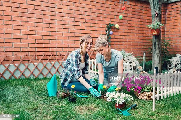 Homosexual Couple Gardening In Their Backyard.