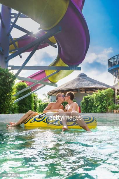 Homosexual couple - men - having fun in waterpark