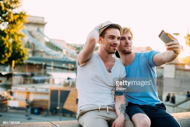 Couple homosexuel prenant selfie près du célèbre pont sur Danube