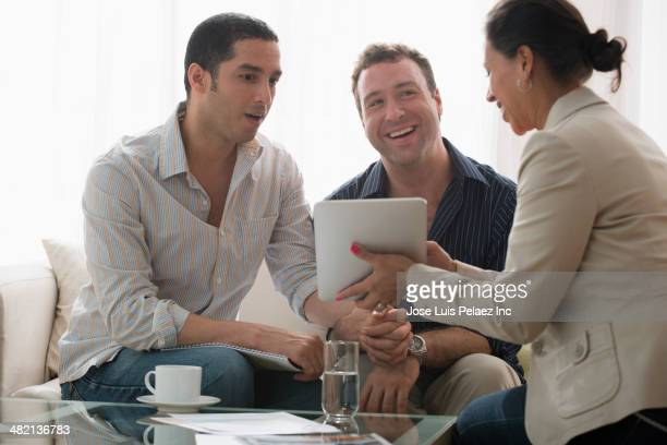 Homosexual couple talking to businesswoman