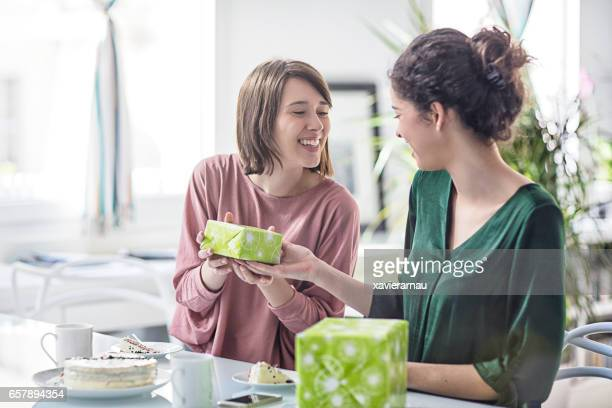 Homosexual woman giving birthday gift to female