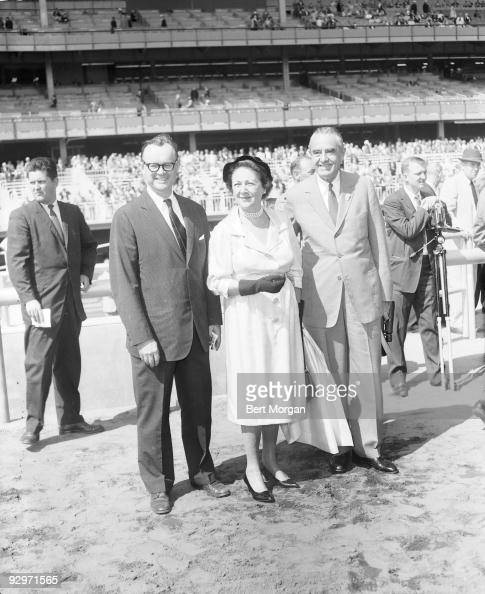 Hon and Mrs William Averill Harriman and Edward T Dickinson standing near the Aquesduct race course on opening day NY September 14 1959