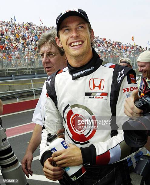 Honda driver Jenson Button of Britain smiles to supporters after winning pole position 11 June at the Formula One Grand Prix of Canada on the Curcuit...