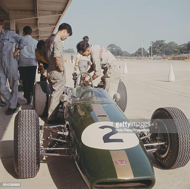 Honda mechanics work on the Brabham BT18 Cosworth SCA of Denny Hulme during the Grand Prix de L'ile de France at the Autodrome de LinasMontlhery near...
