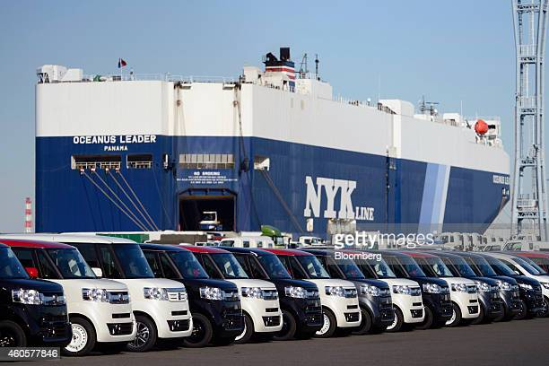 Honda Motor Co automobiles bound for shipment sit at a yard in front of Nippon Yusen KK's Oceanus Leader vehicle carrier ship in Yokohama Japan on...