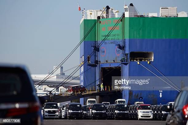 Honda Motor Co automobiles bound for shipment sit at a yard in front of a Nippon Yusen KK vehicle carrier ship in Yokohama Japan on Monday Dec 15...