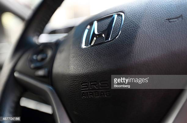 A Honda Motor Co badge and airbag unit for the drivers seat are seen on the steering wheel of a Fit Hybrid vehicle in Tokyo Japan on Thursday Oct 23...