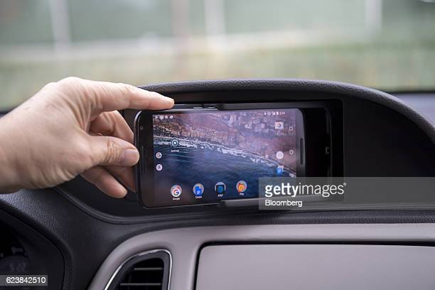 A Honda Motor Co employee points to different incar applications available in a new vehicle during a press briefing at the Honda Silicon Valley Lab...