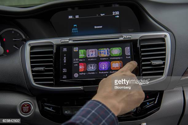 A Honda Motor Co employee scrolls throught different incar applications available in a new vehicle during a press briefing at the Honda Silicon...