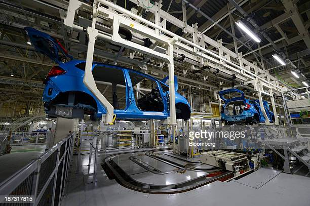 Honda Motor Co Fit vehicles hang from overhead cranes as they move along the production line at the company's Yorii plant in Yorii town Saitama...
