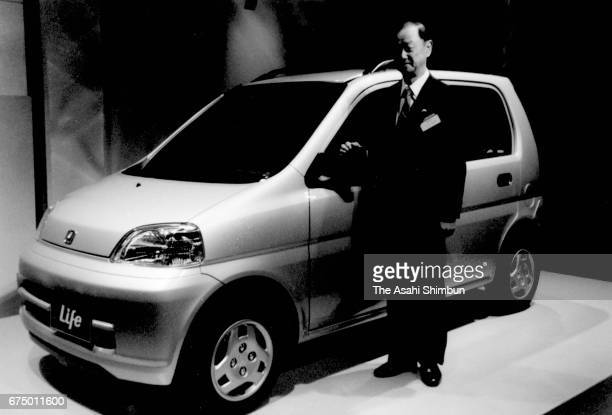 Honda Motor Co President Nobuhiko Kawamoto stands next to the new vehicle 'Life' during its unveiling on April 18 1997 in Tokyo Japan
