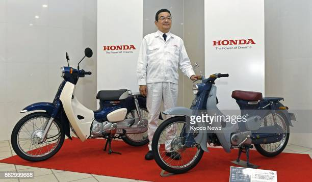 Honda Motor Co President Takahiro Hachigo poses with new Super Cup motorcycle models at the company's factory in Otsu in Kumamoto Prefecture...