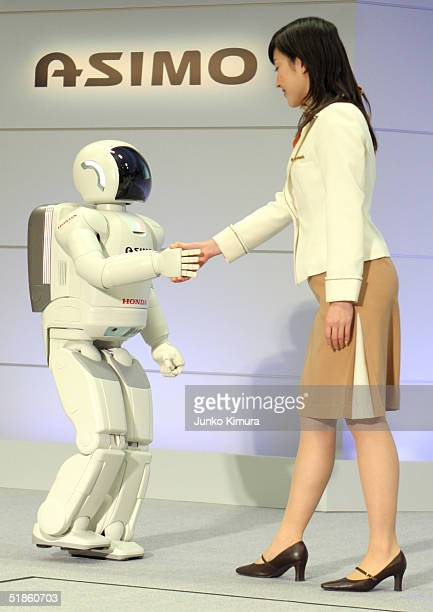 Honda Motor Co's humanoid robot Asimo shakes hands with a woman during a press review December 15 2004 in Tokyo Japan By detecting people's movements...