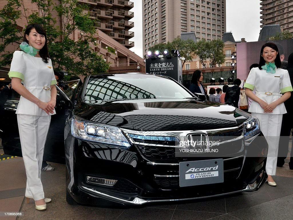 Honda Motor employees introduce the company's new hybrid sedan 'Accord Plug-in Hybrid' in Tokyo on June 20, 2013. The plug-in hybrid model achieves over 70km per litre. AFP PHOTO / Yoshikazu TSUNO
