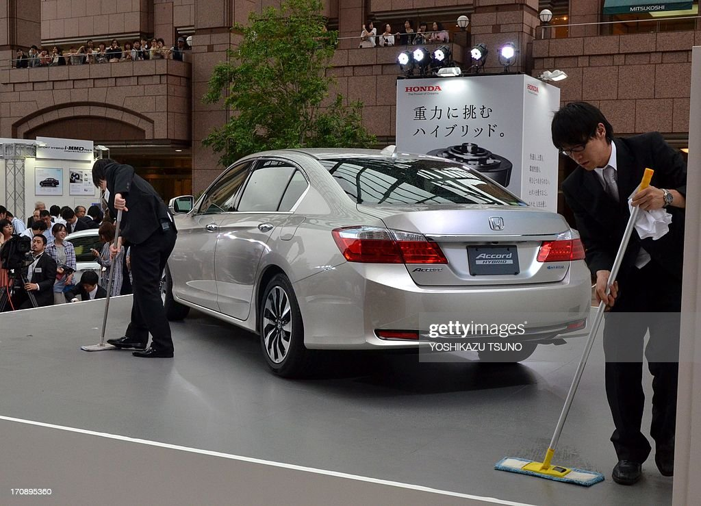 Honda Motor employees sweep the floor before the launch introduce the company's new hybrid sedan 'Accord Hybrid' (C) and 'Accord Plug-in Hybrid' in Tokyo on June 20, 2013. The new Accord Hybrid achieves high economic efficiency of 30 km per litre while the plug-in hybrid model achieves over 70km per litre. AFP PHOTO / Yoshikazu TSUNO