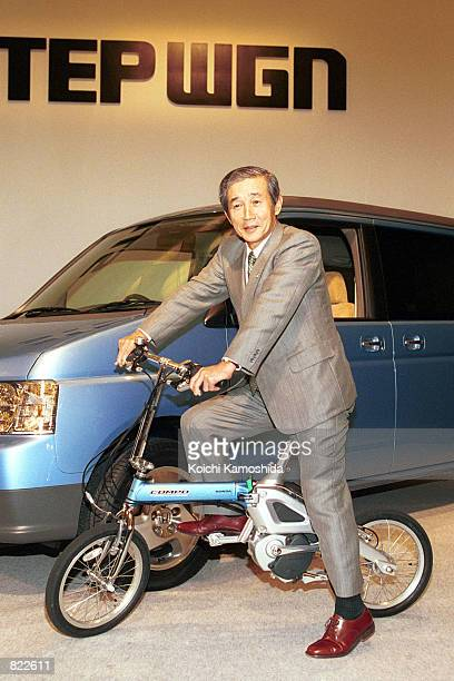 Honda Motor President and CEO Hiroyuki Yoshino sits on the new 'Step Compo' foldable motor assisted bicycle April 5 2001 in Tokyo Japan The bicycle...