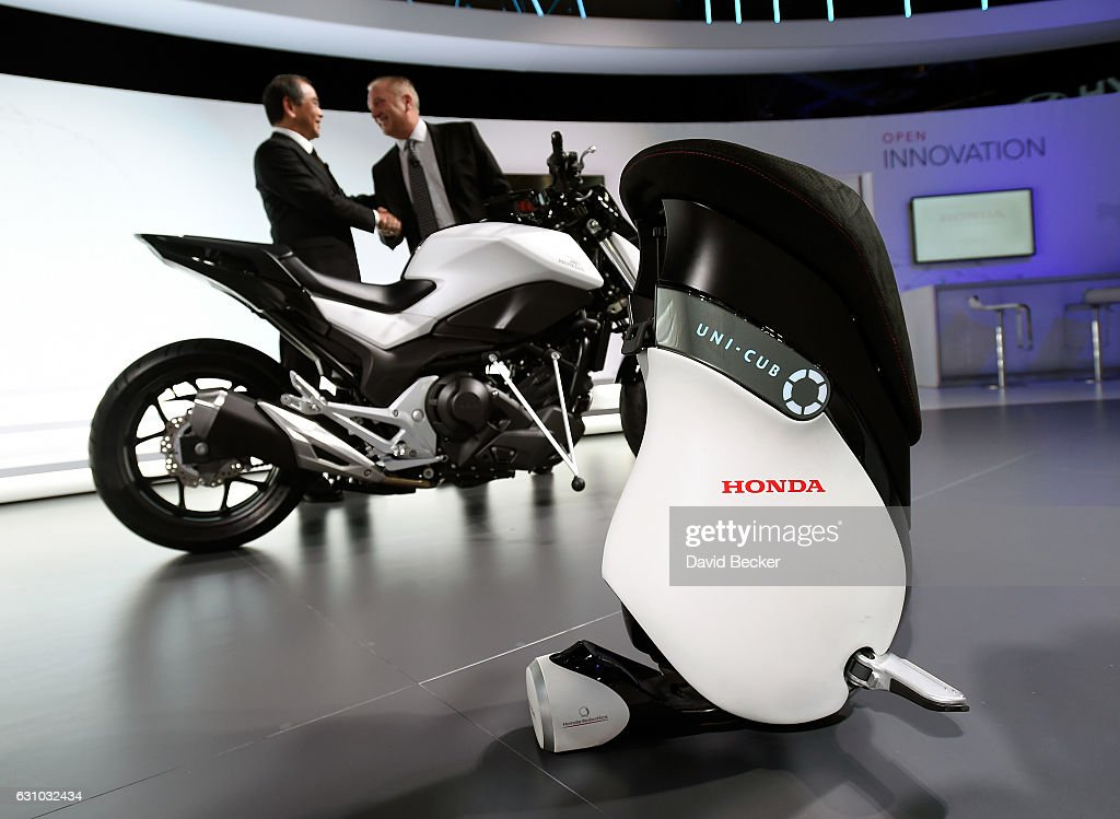Honda Research & Development President Yoshiyuki Matsumoto (L) and Honda Research & Development Americas President Frank Paluch shake hands as the Honda Riding Assist Motorcycle and Uni-Cub are unveiled at a Honda press event at CES 2017 at the Las Vegas Convention Center on January 5, 2017 in Las Vegas, Nevada. CES, the world's largest annual consumer technology trade show, runs through January 8 and features 3,800 exhibitors showing off their latest products and services to more than 165,000 attendees.