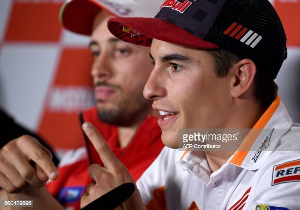 Honda rider Marc Marquez of Spain answers a question beside Ducati rider Andrea Dovizioso of Italy during a press conference at Twin Ring Motegi...