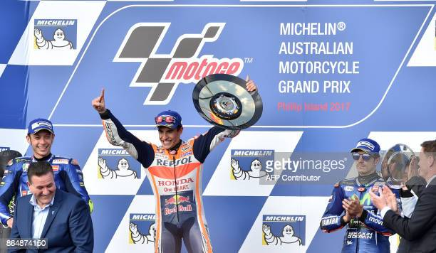 Honda rider Marc Marquez of Spain celebrates his victory on the podium with secondplace Yamaha rider Valentino Rossi of Italy and thirdplace Yamaha...