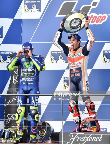 Honda rider Marc Marquez of Spain celebrates his victory on the podium with secondplace Yamaha rider Valentino Rossi of Italy at the end of the...