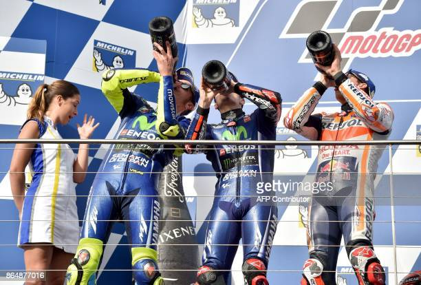 Honda rider Marc Marquez of Spain celebrates his victory on the podium with secondplaced Yamaha rider Valentino Rossi of Italy and thirdplaced Yamaha...