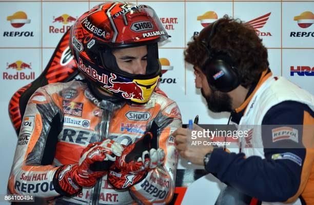 Honda rider Marc Marquez of Spain consults with a team member during the third practice session of the Australian MotoGP Grand Prix at Phillip Island...