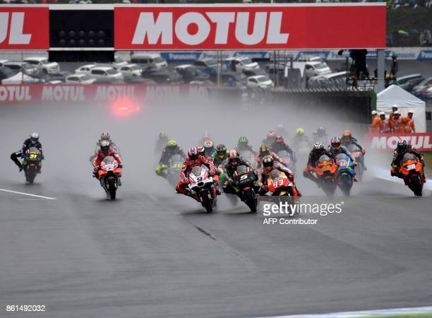 Honda rider Marc Marquez of Spain leads the pack entering the first turn right after the start of the MotoGP Japanese Grand Prix at Twin Ring Motegi...